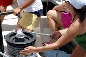 A female guest grinding the winch on an America's cup yacht in St. Maarten