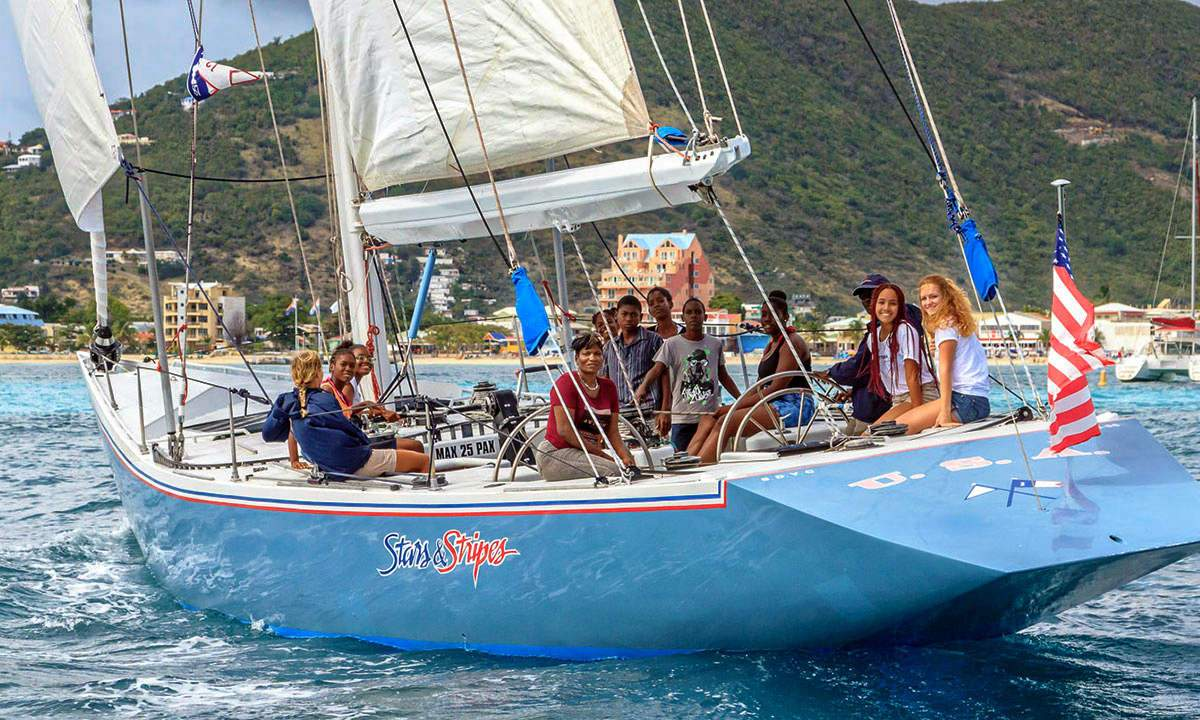 Smiling guests on America's Cup Yacht Stars & Stripes on the water of Great Bay, St. Maarten
