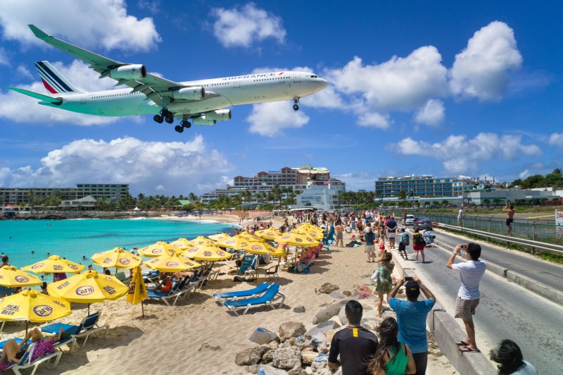 A commercial airline flying over Maho Beach to land at the Princess Juliana International Airport in St Maarten